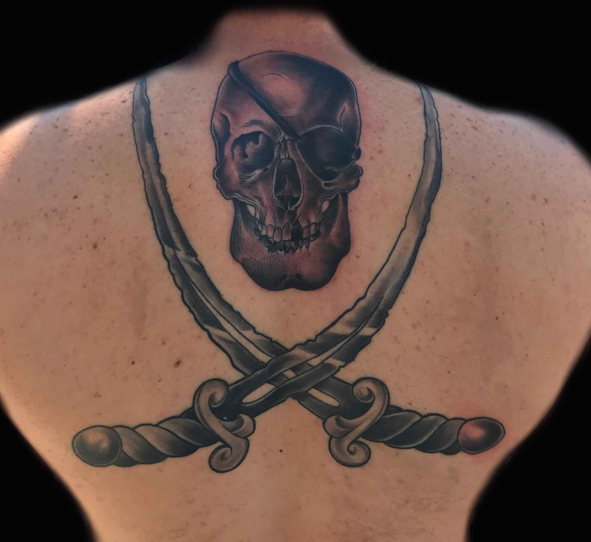 black and gray tattoo of skull snd swords by Roger Solis