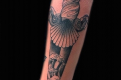 black-and-grey-tattoo-of-wave-with-dagger-on-arm-by-Roger-Solis
